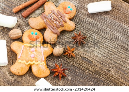 two traditional homemade gingerbread men with spices and marshmallows on wooden table