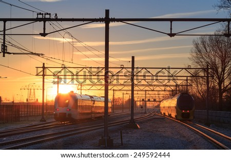 Two trains leaving a railway station during a winter sunrise. - stock photo