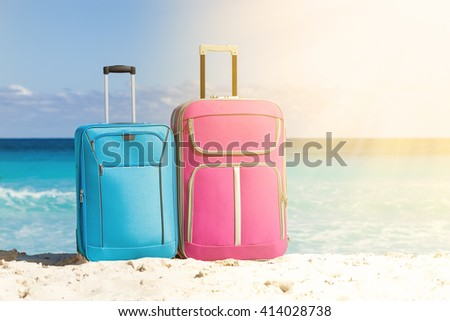 Two travel suitcases of pink and blue color on white sandy beach with turquoise sea background in sun light, copyspace for your text, summer holidays concept