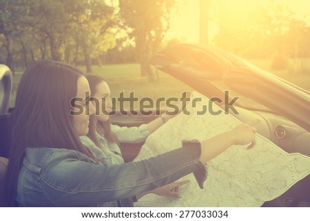 Two traveler woman on the road in cabrio car with map - stock photo