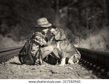 Two travelers - boy and dog sitting on the railway - stock photo