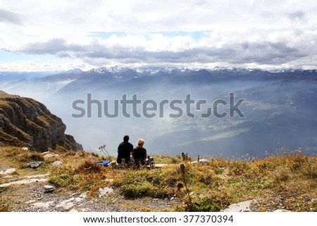 Two trekking people  sitting on the Swiss Alps Chaeserrugg enjoying the dramatic clouds moment