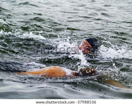 two triathletes on swim-stroke - stock photo