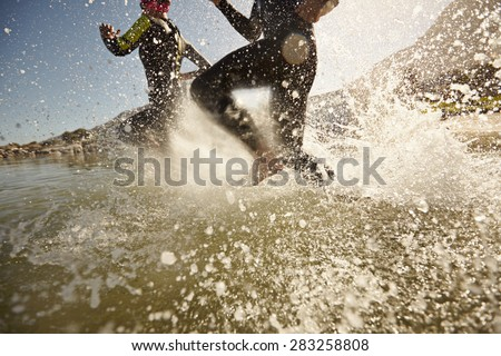 Two triathlon participants running into the water for swim portion of race. Splash of water and athletes running. Focus on water splash. - stock photo
