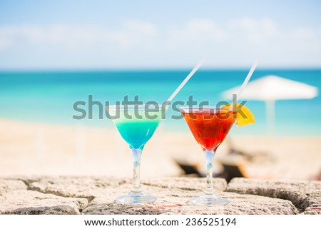 Two tropical cocktails on tropical beach ocean white sand and seascape. Travel, leisure, holiday, paradise getaway, vacation escape, tourism concept - stock photo