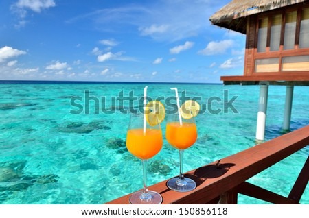Two tropical fresh juices on overwater villa balcony -- Vacation Concept  - stock photo