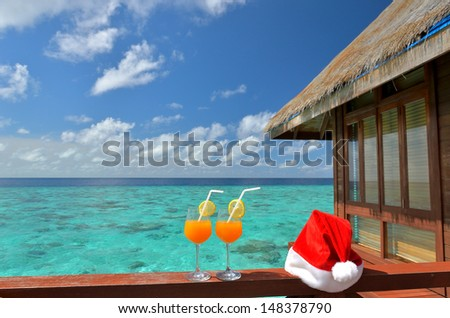 Two tropical fresh juices with santa christmas red hat -- Tropical christmas  - stock photo