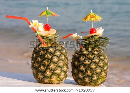 Two tropical pineapple cocktails on the beach - stock photo