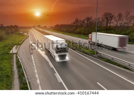 Two trucks driving towards the sun in blurred motion on the freeway at beautiful sunset. Transport scene on the motorway near Belgrade, Serbia. - stock photo
