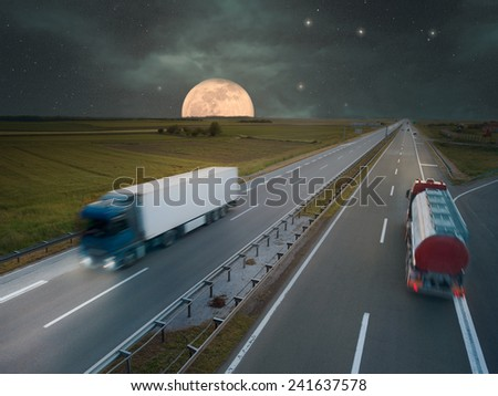 Two trucks in motion blur on the highway at night of the full moon - stock photo