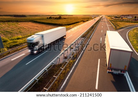 Two trucks on highway in motion blur at sunset - stock photo