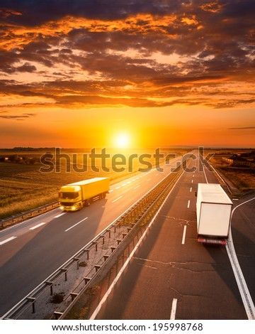 Two trucks on the highway at dusk - stock photo