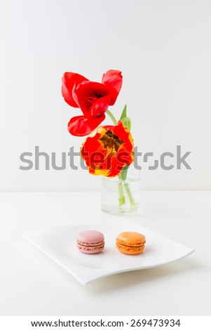 Two tulip flowers in glass vase and two macaroon cookies on a plate. - stock photo