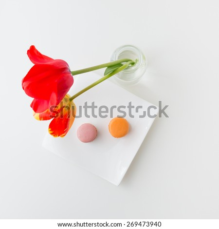 Two tulip flowers in glass vase and two macaroon cookies on a plate, top view. - stock photo