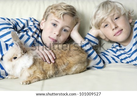 Two twin brothers stroking their pet rabbit on a sofa at home.