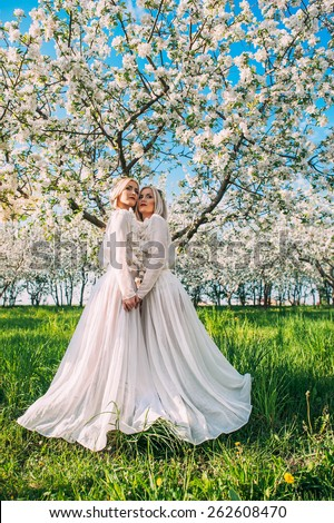 two twin sisters in a cherry orchard - stock photo