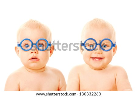 Two twins babies boys wearing glasses. One kid serious, the other child smiling. Young students. Isolated on white background - stock photo