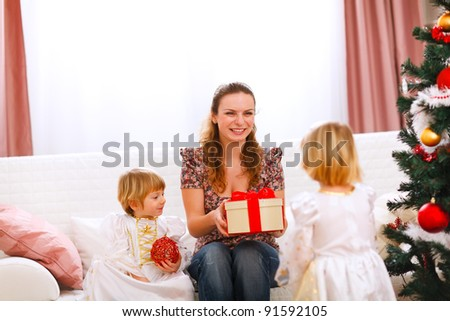 Two twins girl presenting gift to mother near Christmas tree