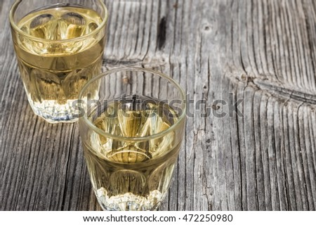 Two typical countryside white wine glasses on wooden background