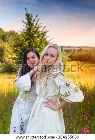 Two ukrainian girls in national costumes at the evening flower meadow  - stock photo