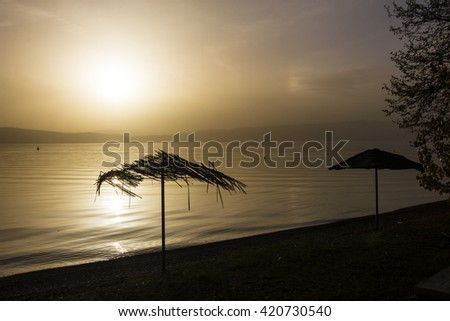 Two umbrellas at the coastline of a lake at sunset - stock photo