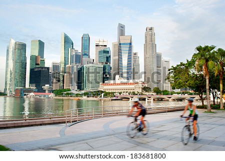 Two unidentified cyclists in Singapore. Singapore downtown on the background - stock photo