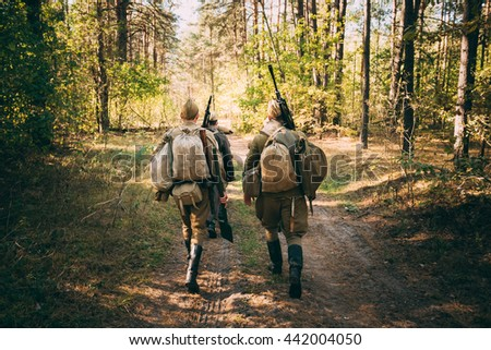 Two Unidentified Re-Enactors dressed As World War II Russian Soviet Soldiers In Camouflage Walks Through Forest On Road - stock photo
