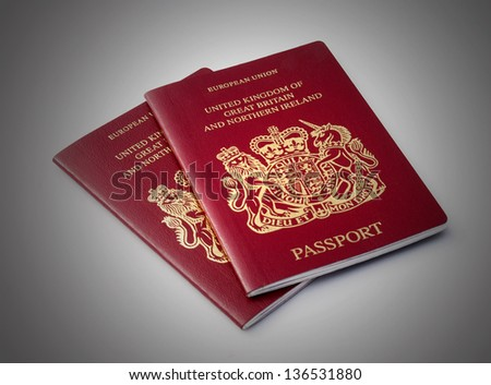 Two United Kingdom passports over plain background