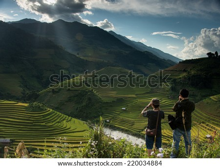 two unknown photographers is taking photos of beautiful rice terrace when the light is shooting at the top of the mountain - stock photo