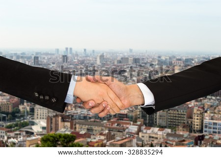 two unrecognizable businessman and businesswoman shaking hands over a cityscape in the background - stock photo