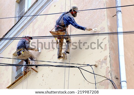 Two unrecognizable painters repair facade - stock photo