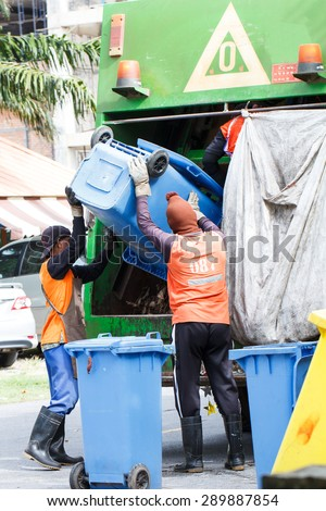 Two urban workers municipal recycling garbage collector truck loading waste and trash bin - stock photo