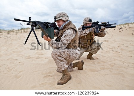 two US marines aim at different directions covering each other - stock photo
