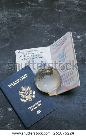 Two US passports on black background. American citizenship. Traveling around the world. Small glass globe on open document. - stock photo