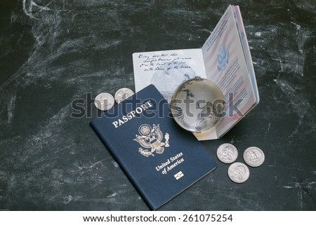 Two US passports on black background. American citizenship. Traveling around the world. Small glass globe on open document. Coins on a side - stock photo