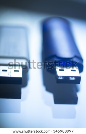 Two USB 3 flash drive III pendrive IT PC memory storage dongle plug socket close-up color artistic photo in blue tones.