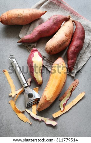 Two varieties of sweet potatoes on grey background - stock photo