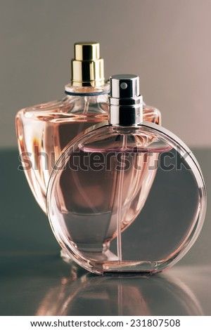 Two various bottles of woman perfume on dark gray background. Toned image. - stock photo