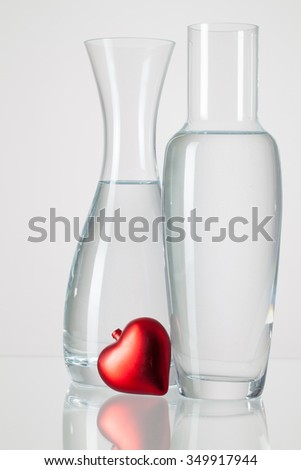 Two vases with clean water and red heart  on a glass table - stock photo