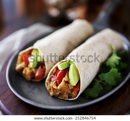 two vegan burritos with avocado, tomato and lentils - stock photo