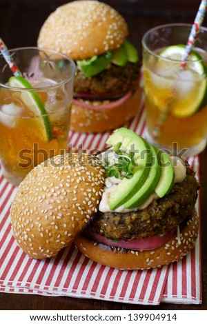 Two vegetarian sweet potato bean burgers with avocado on sesame buns, with one upper bun tilted to showcase the layers. Served with iced tea on a sheet of candy-stripe napkin - stock photo