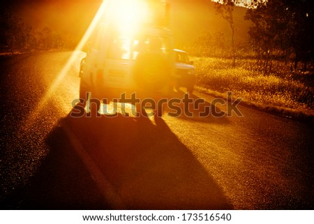 Two vehicles passing on a bend at sunset, sun is pouring into picture, with an instagram effect. - stock photo