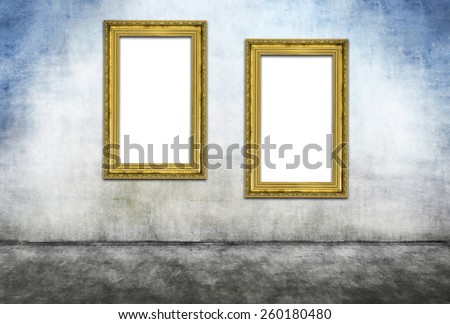 Two vertical golden frames on gray dirty wall - stock photo