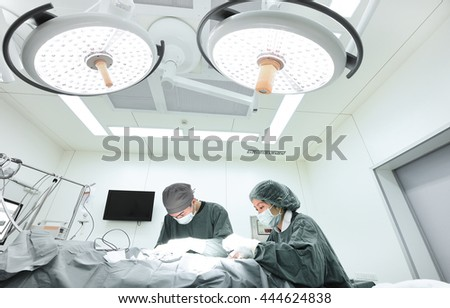 two veterinarian surgeons in operating room take with selective color technique and art lighting - stock photo