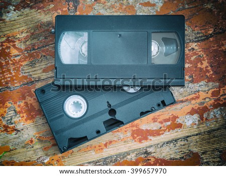 Two video cassette close-up on a wooden table, retro-styled, old, record sound and images