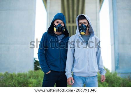 Two Vietnamese young people in gas masks - stock photo