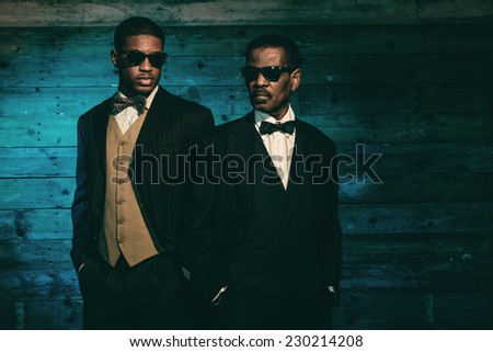 Two vintage african american gangsters in front of old wooden wall. Wearing black sunglasses and suit. - stock photo