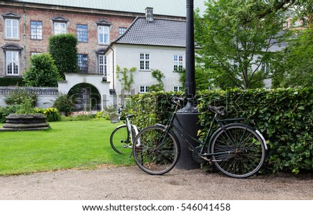 Two vintage bicycle in beautiful historical green garden with old buildings in the background / Two Vintage Bicycles in Garden