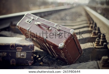 Two vintage brown suitcases are left to lie on railway rails. - stock photo