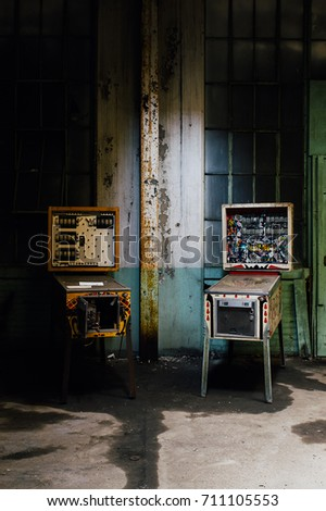 Two vintage but broken pinball machines were left behind at a break room inside an abandoned clothing factory.